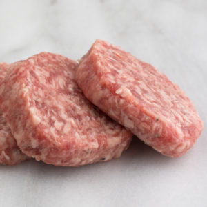 Fresh sausage patties on a marble cutting board side view.